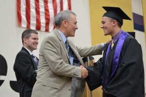 Steve Tenpas, Vice President of the Board of Education, embraces his son, Nolan Tenpas, on stage at the graduation ceremony.