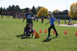 Physical education teacher David O'Keefe; 6th graders Carolina Munoz (kneeling) and Ellie Michaels (kicking)