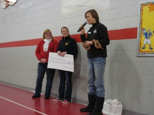 Chris Carlson and Kris Harbort present a check for $1,200 to Emily Steinwehe, Shelter Educator with the Dane County Humane Society