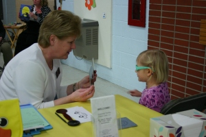 Kathy Feltz from Essential Family Vision, provides vision screening to a 4-year-old child