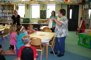 Louise Valdovinos, Children's Librarian at the  DeForest Area Public Library, explains activity stations, such as butter churning, Palmer method of cursive writing, and more.