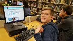 High school boy looking up at camera after earning an Hour of Code certificate.