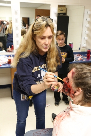 Jan Williams applying make-up to Kayla Doucette in preparation for the mock car crash as Lance Furseth looks on