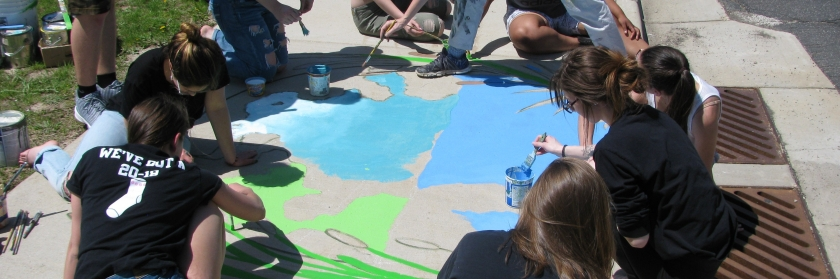 Students painting in front of stormwater drain