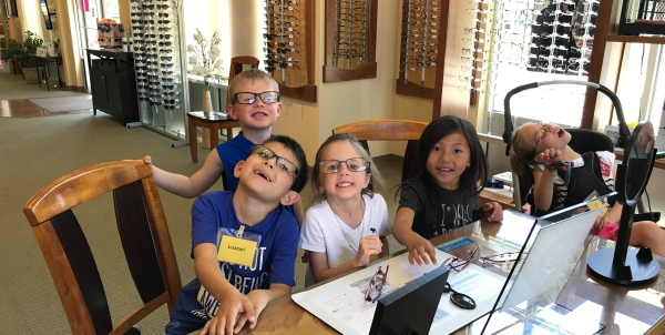 five students at Essential Family Vision trying on eye glasses