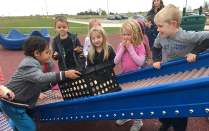 Students pushing a crate up a slide
