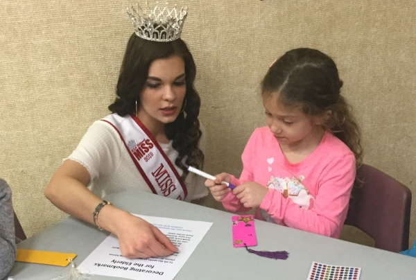 Miss Wisconsin working with a student