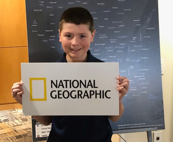 Bennett Morrison holding a National Geographic sign