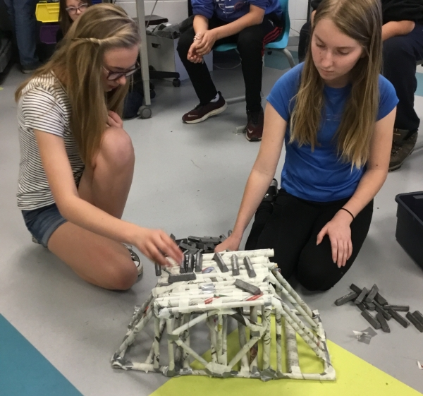 Two girls building newspaper tower