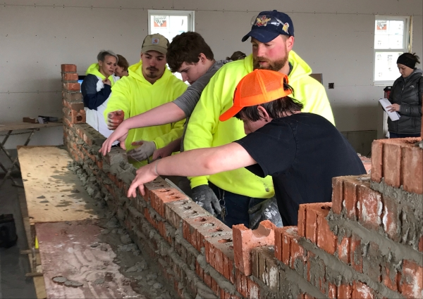 students working with adults laying bricks