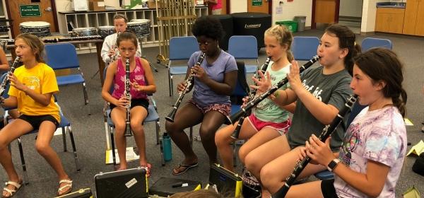 Six girls each playing a clarinet