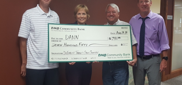 Four people holding large check