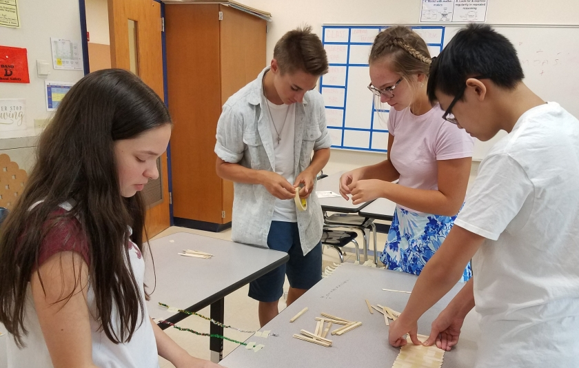 students building bridge with popsicle sticks