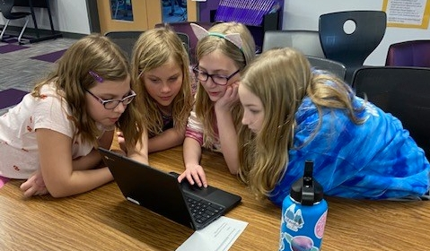 Four students looking at and using a laptop
