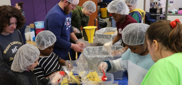 students and staff packing meals