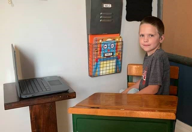 Young boy sitting at desk with computer